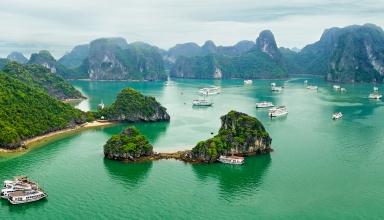 Tourists boats exploring Halong Bay 384x220 - خلیج هالونگ ، از جاذبه های محبوب ویتنام | Ha Long Bay